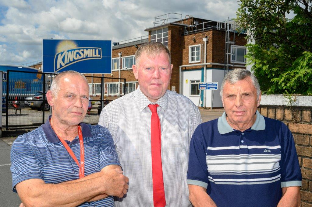 Three men stood infront of a factory with the Kingsmill logo behind them