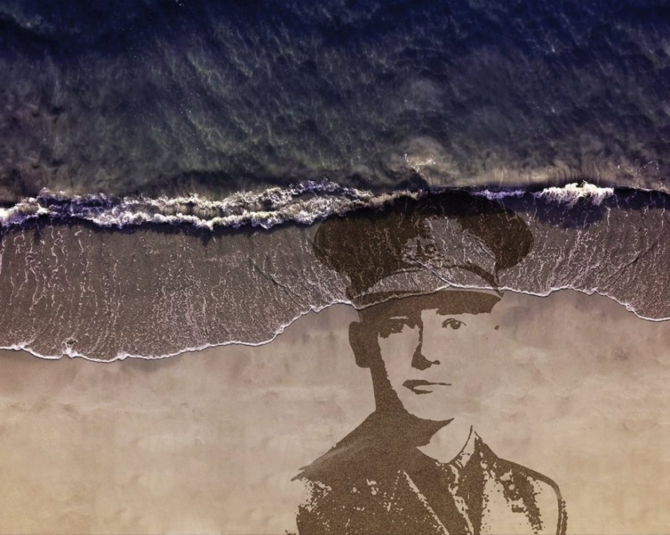 Sand portrain of WW1 soldier being washed away with the tide