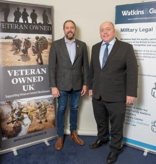 Scott Johnson (left) and Clive Thomas (right) stand side by side in front of a Veteran Owned UK sign and a Watkins & Gunn sign.