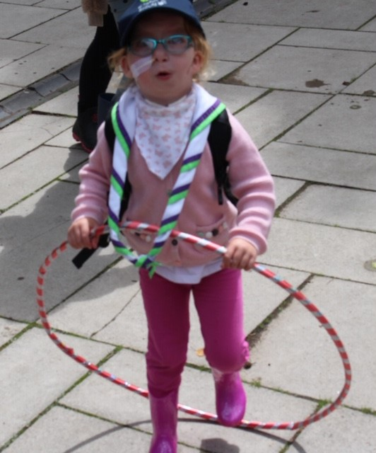 Child playing with a hoola-hoop enjoying the Ty Hafan Scout Group family camp out
